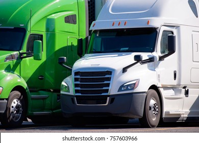 Green and White Big rigs semi trucks of different makes and models stand in row on truck stop parking lot for truck driver rest according to logbook delivery schedule