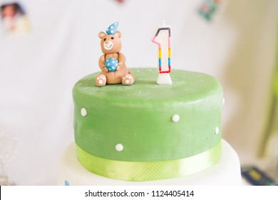 Green and White Birthday Cake with One Year Old Candle and Teddy bear