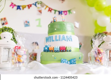 Green and White Birthday Cake with One Year Old Candle with Happy Birthday Banner in the Background