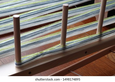 green, white, and blue cotton yarn on a warping frame/board.  Shows the cross (the most important part of handweaving) and three warping pegs.  Backlit by natural light from window