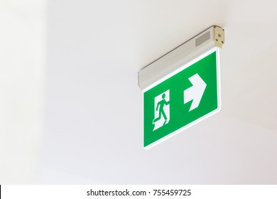 green and white fire exit sign hanginf on white ceiling, ,fire escape electronic sign