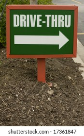Green and white plastic drive-thru sign in the ground