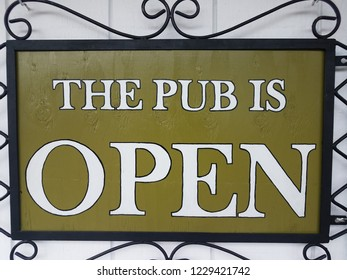 green and white the pub is open sign