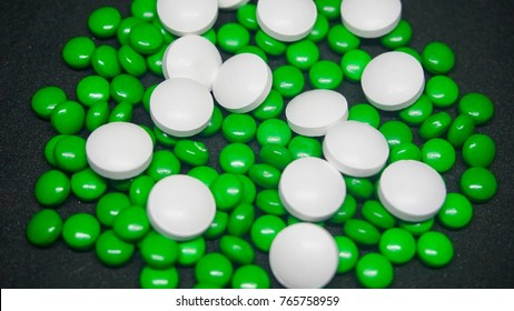 Green and white round pill of medicines in black background.
