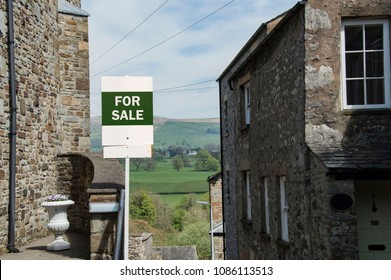 Green And White For Sale Sign With Idyllic Countryside Background On Street Of Beautiful Stone Houses