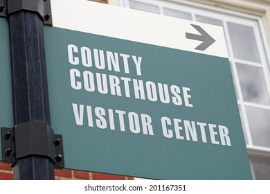 A green and white sign reading County Courthouse and Visitor Center
