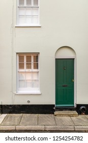 Green and white typical english house facade with door and window viewed from outdoors.