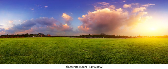 Green wide meadow with grass and colorful cloudy sky at sunset