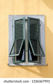 Green window on yellow background (Tuscany Italy). Shutters closed by a hot day