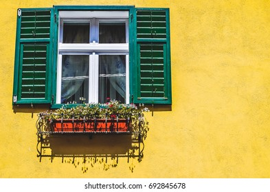 Green window on yellow wall with flowers in the city of Sbiu, Romania
