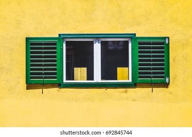 Green window on yellow wall in the city of Sbiu, Romania