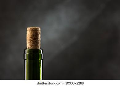 Green wine bottle with cork on dark background, close-up view