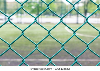 Green wire fence and football field on background