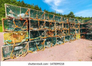 Green wire lobster traps stacked on the ground. Lots of rope on and around the traps. Partially cloudy blue sky above, and trees in the background. Bright sunny day.