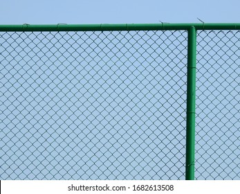 green wire mesh of fence with blue sky background