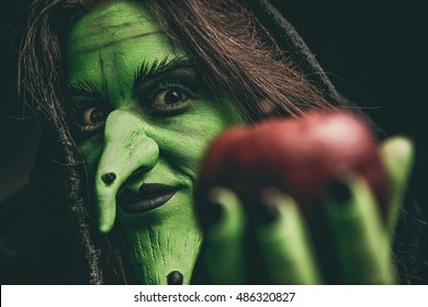 Green witch holding an apple in her hand. Shallow depth of field.