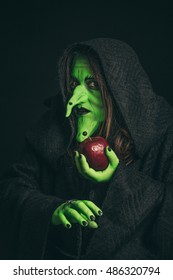 Green witch holding a rotten apple in one hand and a spider in the other