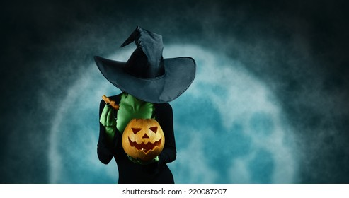 Green witch opening Halloween carved pumpkin on full moon background. Halloween, horror theme