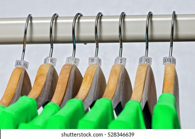 Green women's t-shirts hang on wooden hangers with indexes of the XXS, XS, S, M, L, XL, XXL sizes on a gray background.