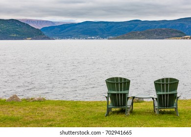 Green wooden Adirondack Chairs in beautiful coastal landscape of Gros Morne National Park, Newfoundland, NL, Canada