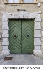 Green wooden door of an ancient building in Tolmezzo city center