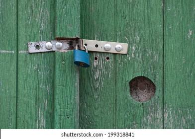 Green wooden door and blue lock