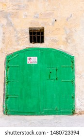 Green wooden door on a traditional Gozo garage with a sign warning people not to park outside it.