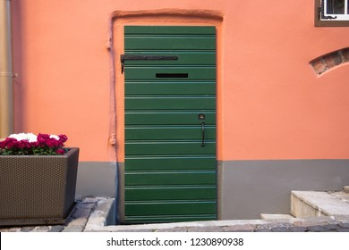 a green wooden door in orange wall
