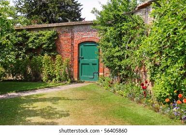 A Green wooden door through an English Walled garden