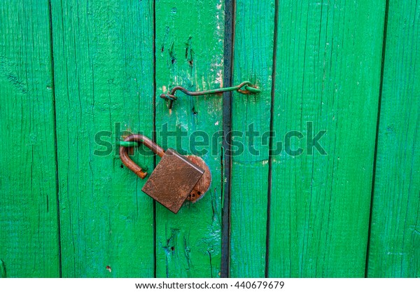 green wooden gate with a padlock and the handle/green old wooden gate