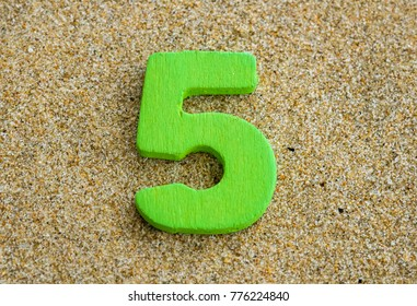 Green wooden of number fi isolated on sand background.
