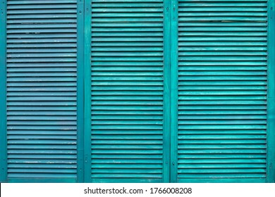 Green wooden shutters. Three wooden casement windows to block sunlight. Background with textured narrow boards of turquoise color. Old green wooden shutters tiled
