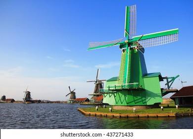 Green wooden Traditional wind mills near windy lake in Zaanse Schans, Netherland
