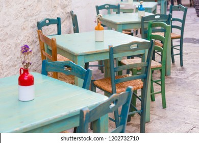 Green wooden vintage outdoor tables and chairs of an italian restaurant in Locorotondo, Puglia, Italy
