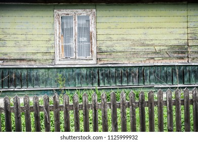 Green wooden wall with a window and fence
