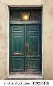 Green wooden weathered door in old building facade. Tallinn, Estonia
