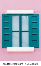 green wooden window on pink wall