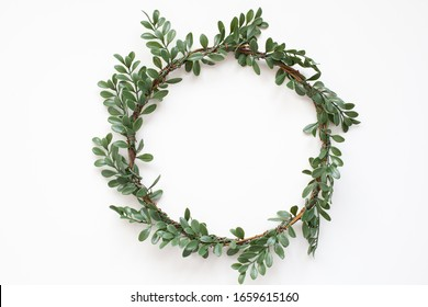 Green wreath with leaves on white background. Wreath made of branches. Flat lay, top view, copy space. Spring composition. Flowers composition. Easter. Boxwood wreath for Christmas. Scandinavian style