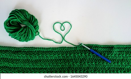 Green yarn being crocheted into a nice scarf with a white background