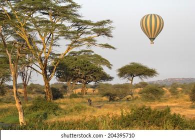 Green and yellow balloon flying over the savannah of Serengeti National Park, Tanzania