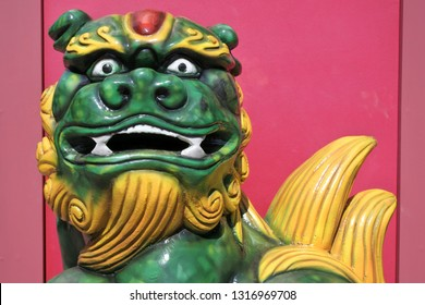 Green and yellow Chinese guardian dragon statue against a red temple wall