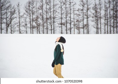 Green and yellow cloth Woman on pine trees and white snow background