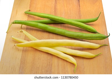 Green and yellow fresh beans on a wooden board