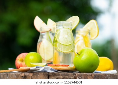 Green and yellow lemon with  green and red apples in soda bottles on bokeh background
