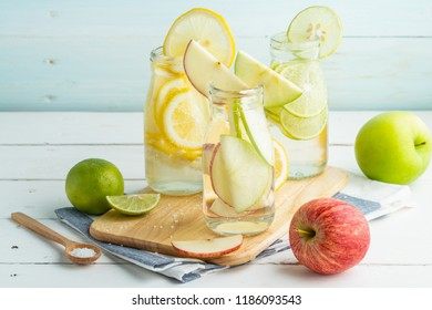 Green and yellow lemon with  green and red apples in soda bottles on cutting bord and white table