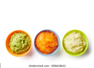 Green, yellow and orange baby puree in bowl isolated on white background, top view; copy space