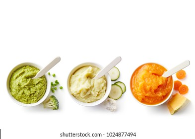 Green, yellow and orange baby puree in bowl isolated on white background, top view