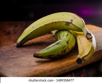 Green and yellow plantain / banana on a wooden table. (organic healthy food recipe)
