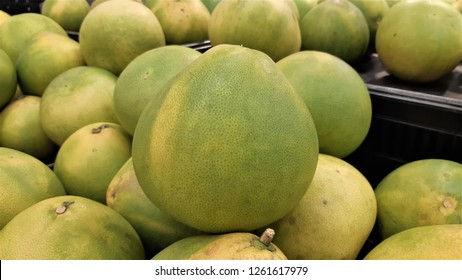 Green and yellow pomelo closeup with many pomelo background