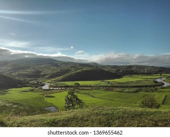 green and yellow rice field in the country side of Madagascar, Africa, during rain season. View of valley and plain under beautiful grey cloudy sky
